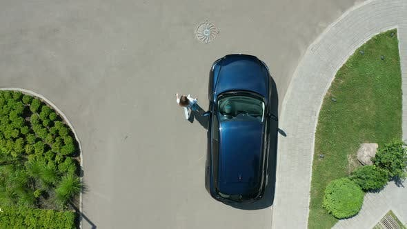 Thumbnail for Drone Shot of Female Walking From Car To Hotel
