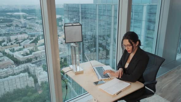 Thumbnail for Young Business Woman Working on a Laptop in a Modern Office Located on the High Floor of a