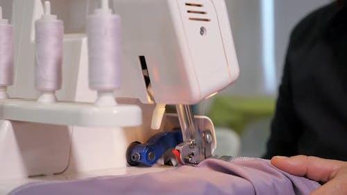 Seamstress Works at Sewing Machine Makes Straight Seams on Cloth, Hands Closeup.