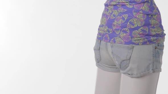 Rotierende Schaufensterpuppe in kurzen Shorts.