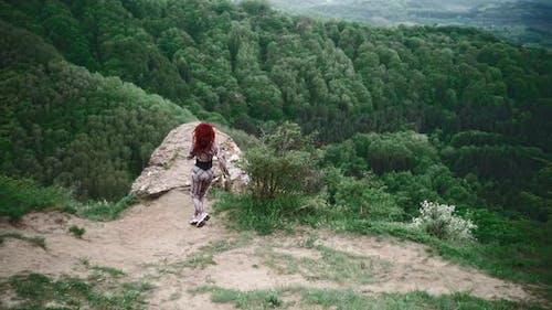 Athletic Girl Runs Along Top Mountain