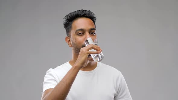 Thumbnail for Happy Young Indian Man Drinking Water From Glass