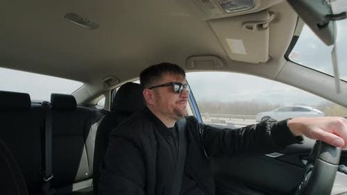 View of Man Driving Car in Day Time Hand on Steering Wheel