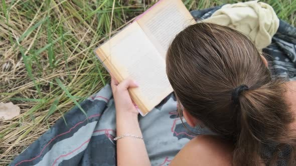 Young Woman Reads a Book Lying in the Grass on Nature at Summer Day.