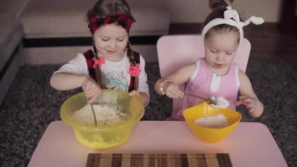 Thumbnail for View From Above of Two Girls Mixing Dough in Bowl at Kitchen