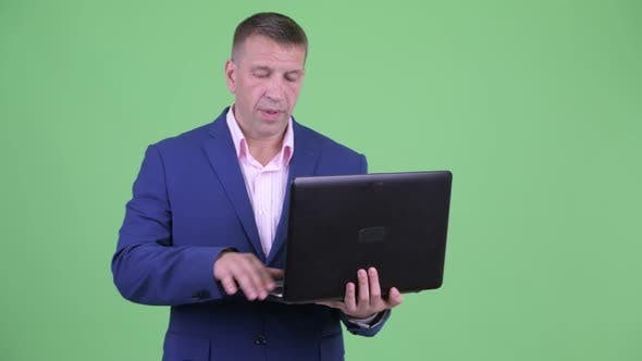 Thumbnail for Mature Macho Businessman in Suit Talking While Using Laptop