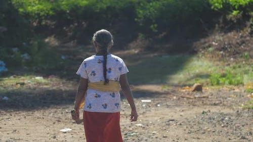 Senior Woman in Skirt with Machete Walks Along Dirty Road