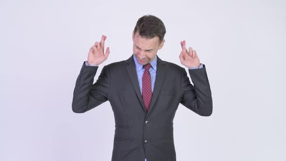 Thumbnail for Studio Shot of Businessman Wishing with Fingers Crossed