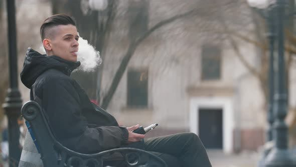 Cover Image for Snappy Brunet Man Sitting and Smoking E-cigarette Outdoors in a Park in Spring