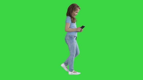 Thumbnail for Little Girl Is Playing with Smartphone While Walking on a Green Screen, Chroma Key
