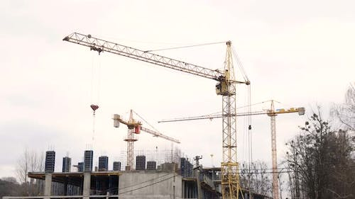 Construction industry. Three cranes and a group of workers are building a house.