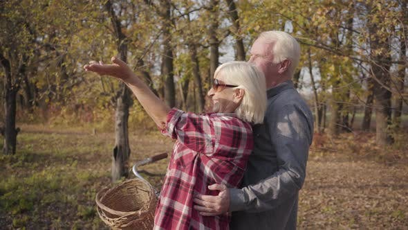 Cover Image for Happy Caucasian Retired Couple Standing in Sunlight in the Autumn Forest or Park and Smiling