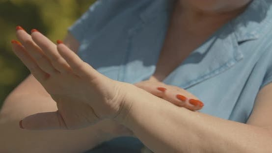 Thumbnail for Unrecognizable Senior Woman Applying Sunscreen Outdoors. Female Caucasian Hands Rubbing Moisturizer