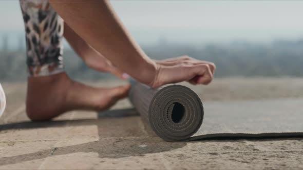 Woman Hands Rolling Up Yoga Mat After training.Girl Folding Fitness Mat Outdoors