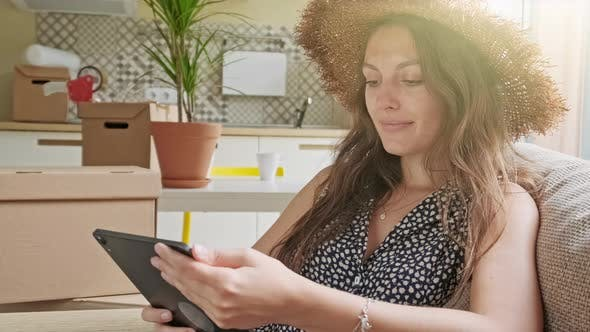 Thumbnail for Woman Using Tablet with Boxes at the Back. Portrait of Young Beautiful Woman with Mobile Phone in