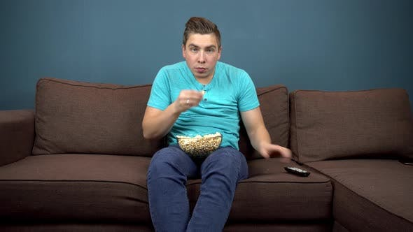 Thumbnail for A Young Man Is Watching TV and Eating Popcorn. The Guy Is Watching TV Carefully. An Exciting Moment