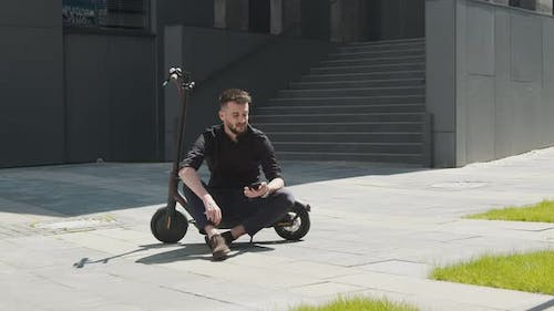 Male Student Sitting on an Electric Scooter in the Middle of the Street and Holding a Mobile Phone
