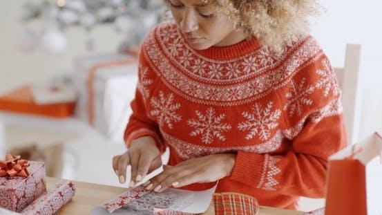 Thumbnail for Junge Frau sorgfältig wickelt ein Weihnachtsgeschenk