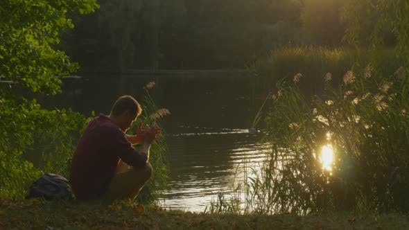 Thumbnail for Man is Sitting at The Lake Bank With His Hands