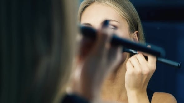 Thumbnail for Attractive Girl Doing Makeup In a Mirror