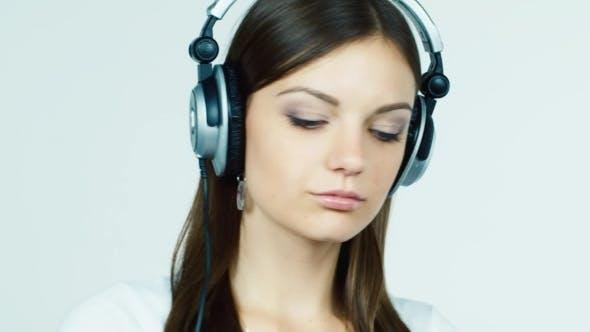 Thumbnail for Brunette In Headphones Smiles Flirting