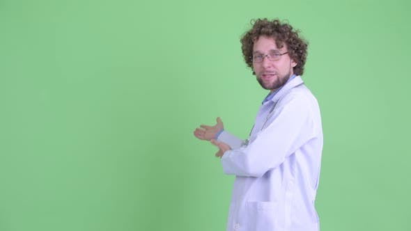 Thumbnail for Happy Young Bearded Man Doctor Talking While Showing Something To the Back
