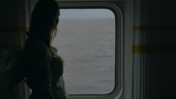 Thumbnail for Girl Opening Blind In Cabin To Look At The Sea