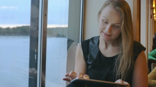 Thumbnail for Woman Sitting Near The Window And Using Tablet