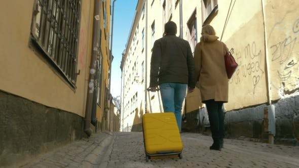 Thumbnail for Couple Of Tourists With Roll-on Bag Walking In Old