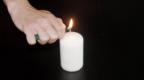 Male Hand Lighting Candle With Lighter Black Bg