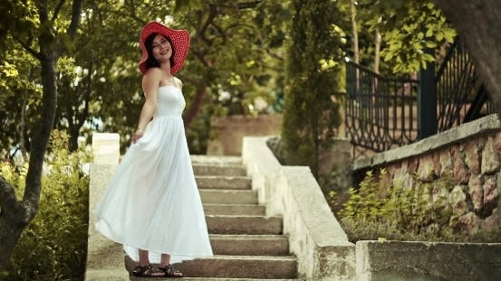 Thumbnail for Asian Girl In a White Dress Poses At a Stone