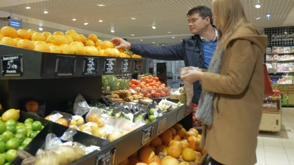 Thumbnail for Happy Couple Choosing Oranges In Supermarket