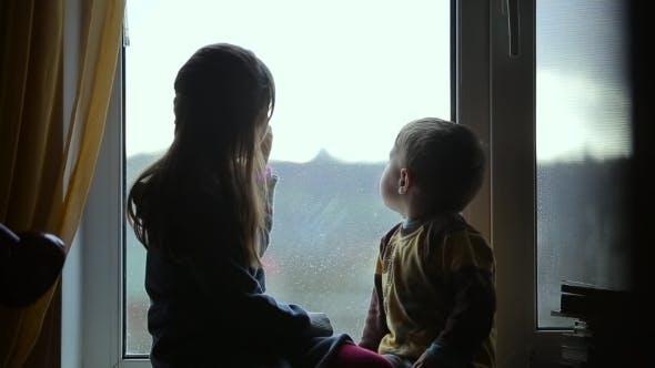 Children Sitting On The Windowsill