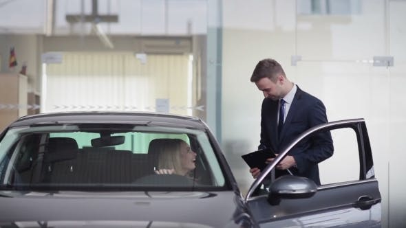 Cover Image for Young Salesman Explaining Information About a Car