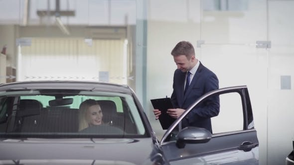 Thumbnail for Cheerful Manager Helping Girl With Choosing Car