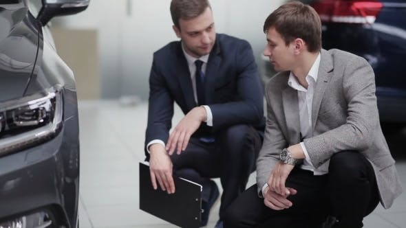 Cover Image for Seller And Buyer Having Conversation Near Wheel