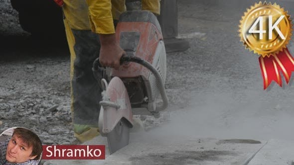 Man Worker in Yellow Workwear is Grinding The