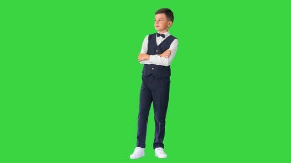 Kleiner Junge in einer Fliege steht mit verschränkten Armen und schaut auf einem Greenscreen-Chroma-Key nach oben