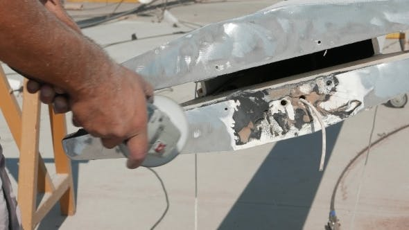 Thumbnail for Worker Sanding Yachts Mast With Angle Grinder