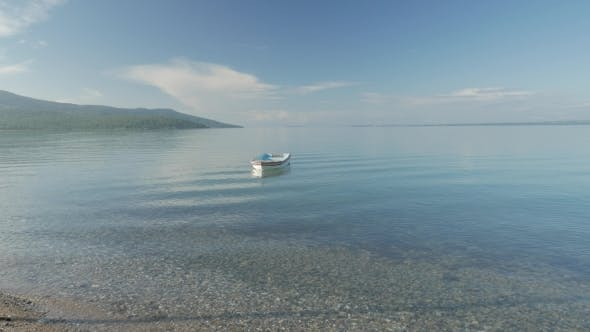 Thumbnail for Lonely Row Boat Floating On Clear Water With Small