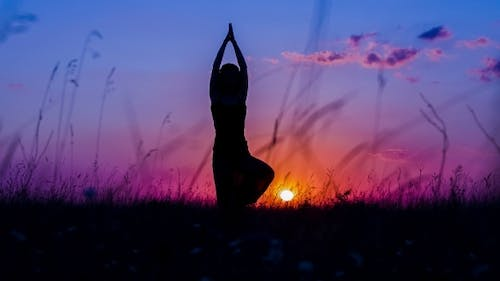 Silhouette Of a Young Girl Doing Yoga Tree Pose At