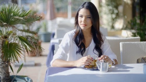 Woman Waiting For Friend In Cafe