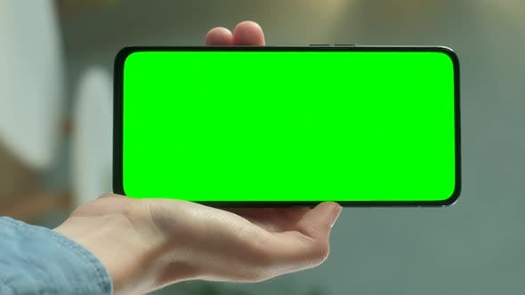 Thumbnail for Young Woman at Home Holding Chroma Key Green Screen Smartphone Watching Content Without Touching or