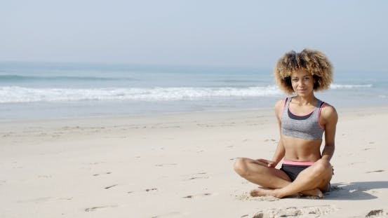 Thumbnail for Woman Sitting On The Beach In Lotus Pose