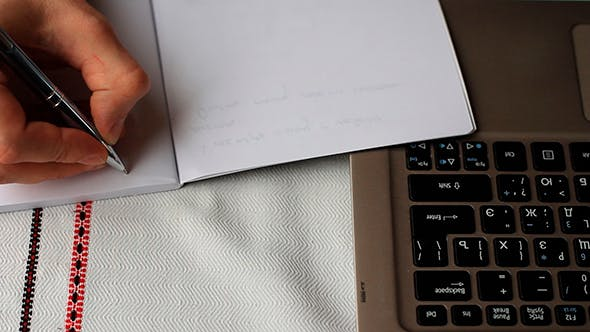 Thumbnail for Man Working On Laptop And Writing In a Notebook
