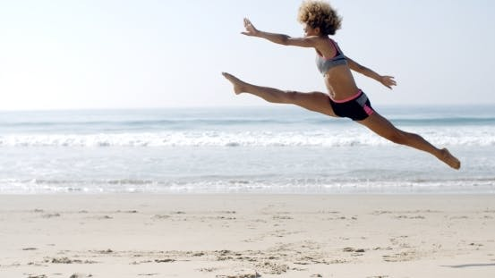 Thumbnail for Happy Young Woman Jumping On The Beach