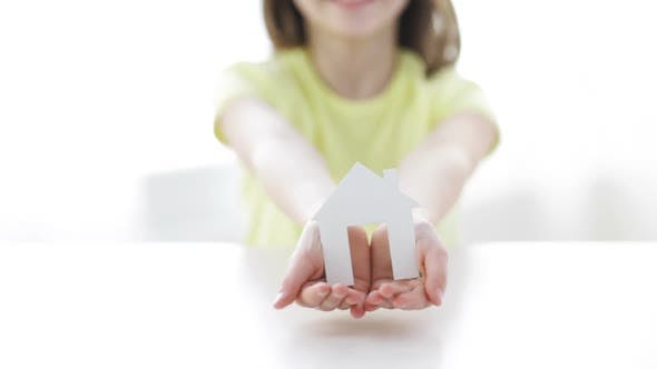 Thumbnail for Close-Up Of Smiling Girl Holding Paper House 1