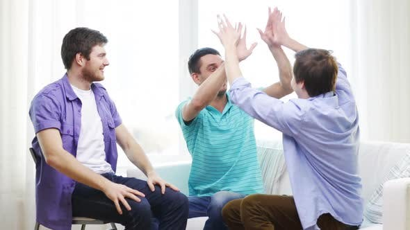 Thumbnail for Smiling Male Friends Giving High Five At Home