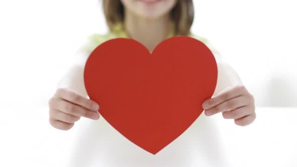 Thumbnail for Close-Up Of Smiling Girl With Red Heart At Home
