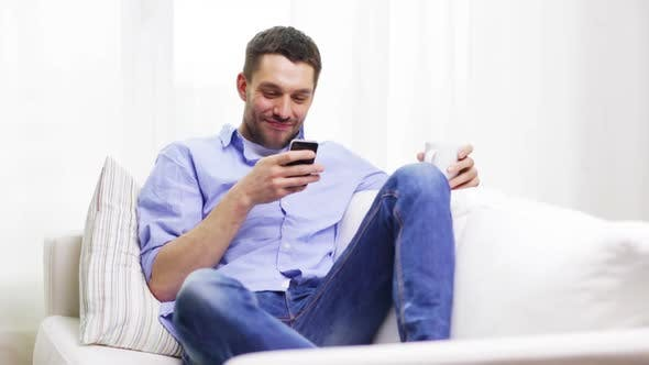 Thumbnail for Lächelnder Mann mit Smartphone und eine Tasse zu Hause